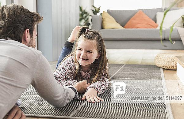 Junger Mann und kleines Mädchen liegen am Boden  Armdrücken