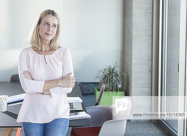 Geschäftsfrau im Büro denkt