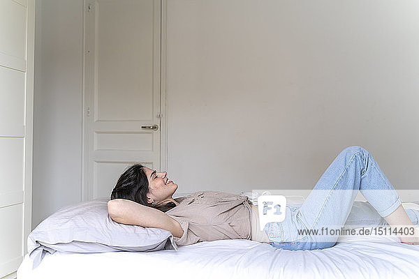 Happy young woman lying on bed with closed eyes