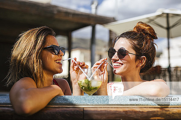 Two women having a drink in a jacuzzi