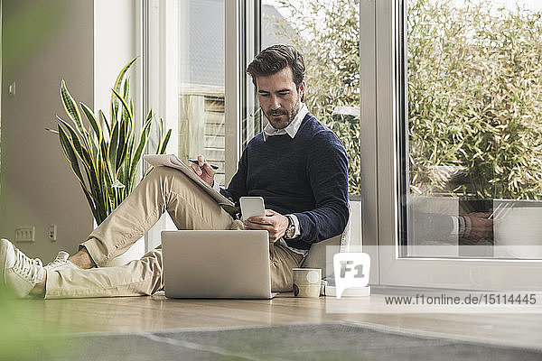 Young man sitting in living room  leaning on window  working with laptop  taking notes