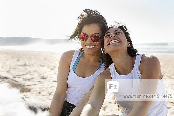 Porträt von zwei glücklichen Freundinnen am Strand
