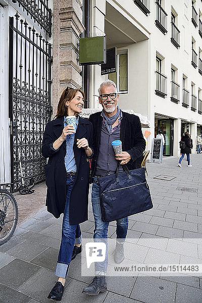 Lächelndes reifes Paar mit wiederverwendbaren Bambusbechern beim Spaziergang durch die Stadt
