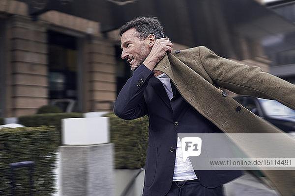 Reifer Mann  der seinen Mantel anzieht