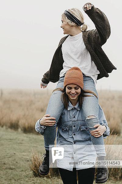 Großbritannien  Schottland  Isle of Skye  glückliche Frau  die ihren Freund huckepack durch die ländliche Landschaft trägt