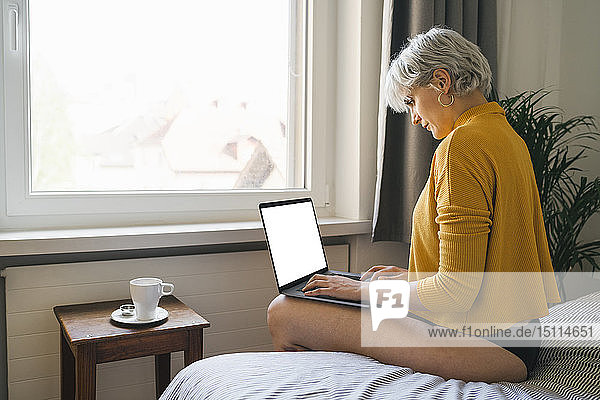 Woman sitting on bed at home using laptop
