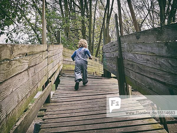 Rückenansicht eines rennenden kleinen Jungen auf dem Spielplatz