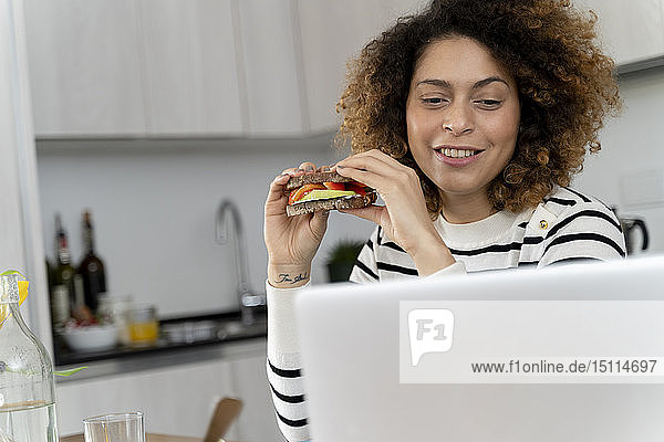 Woman using laptop  while eating a sandwich
