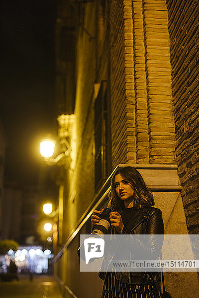 Young woman with camera on the street at night
