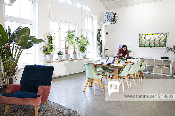 Frau arbeitet am Tisch in einem modernen Büro