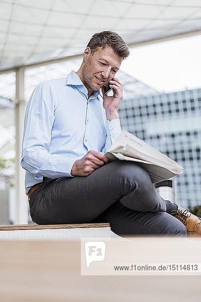 Geschäftsmann draußen in der Stadt am Handy