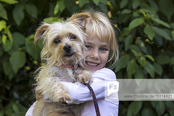 Portrait of happy little girl with her dog