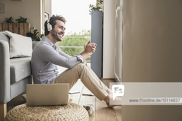 Young man sitting at home on floor  using laptop  listening music