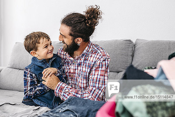 Father and son sitting together on the couch folding laundry