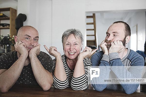 Porträt von erwachsenen Söhnen mit lachender älterer Mutter  die mit dem Kopf in der Hand zu Hause am Tisch sitzt
