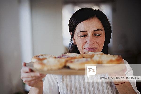 Reife Frau serviert hausgemachte Kuchen auf einem Holztablett