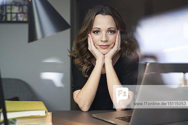 Porträt einer Frau mit Laptop hinter einer Fensterscheibe