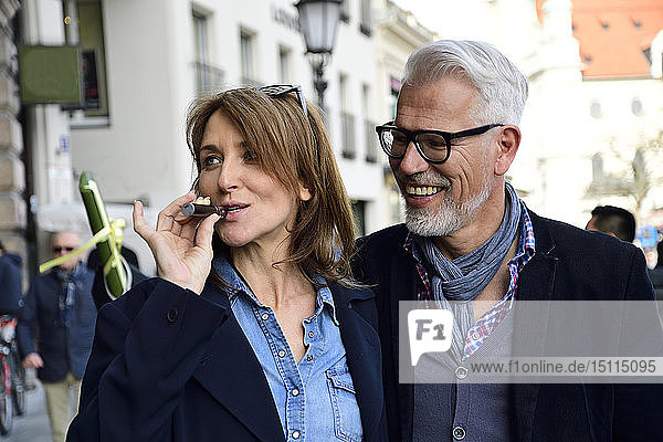 Mature couple walking in the city  woman smoking electronic cigarette
