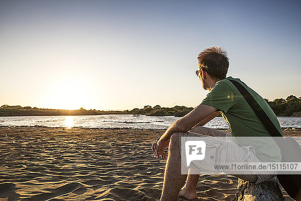 Italy,  Sicily,  young man enyoing the sunset at the beach of Eloro
