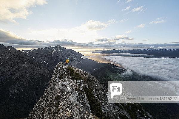 Österreich  Tirol  Gnadenwald  Hundskopf  männlicher Bergsteiger im Fels stehend im Morgenlicht