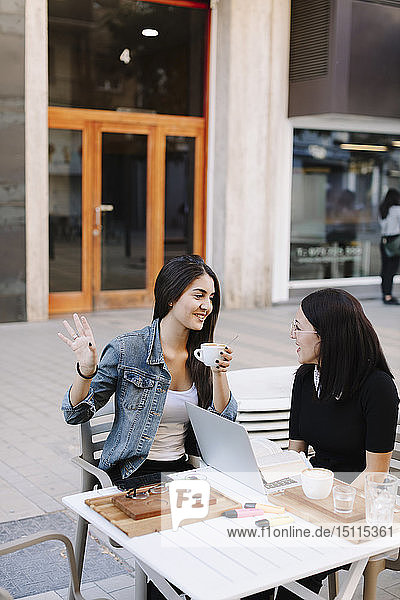 Zwei Freunde sitzen mit Laptop in einem Straßencafé zusammen