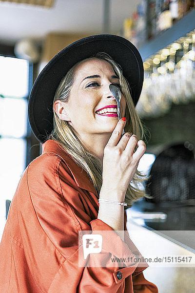 Verspielte Frau mit einem Löffel in einem Café