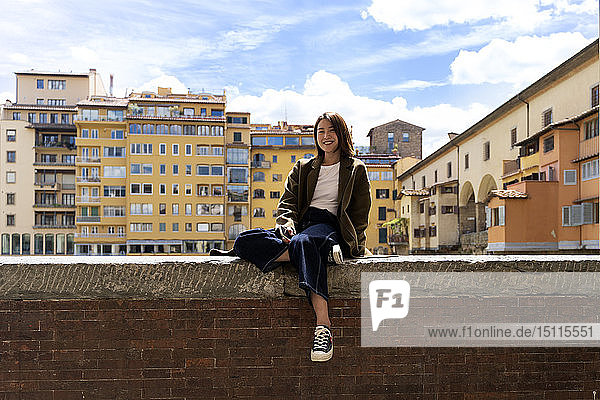 Italy  Florence  smiling young woman resting on a wall in the city