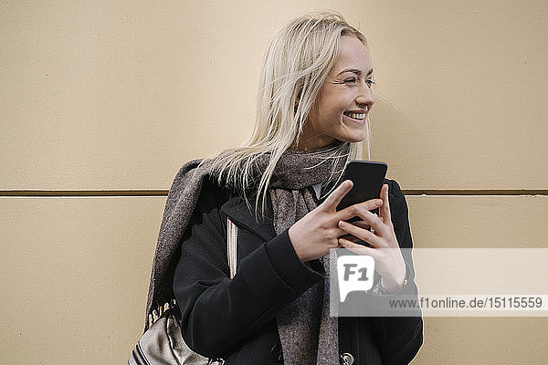 Lächelnde junge Frau mit Handy an der Wand
