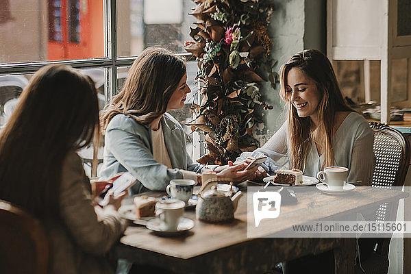 Drei glückliche junge Frauen mit Handy-Treffen in einem Cafe