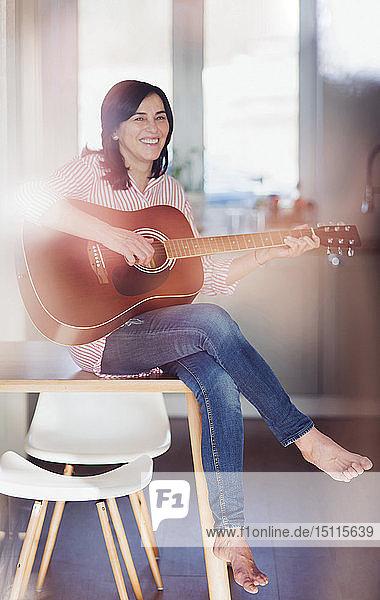 Lächelnde reife Frau spielt zu Hause Gitarre