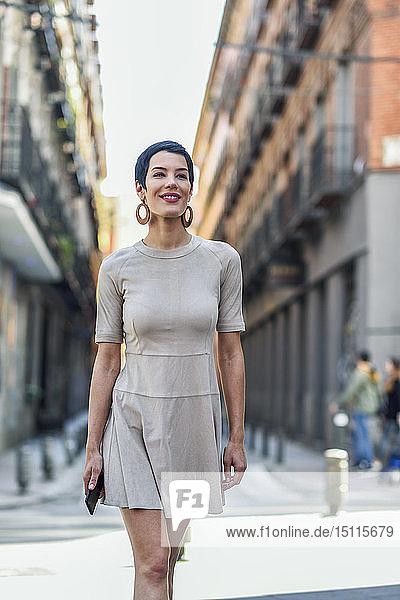 Modische junge Frau in einem Kleid geht in der Stadt spazieren