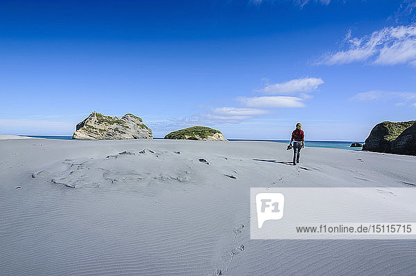 Woman walking in the white sand dunes on Wharariki Beach  South Island  New Zealand