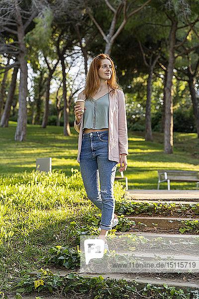 Junge rothaarige Frau mit Kaffee zum Parkbesuch
