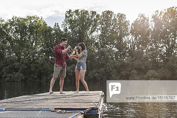 Happy young couple having a drink on jetty at a remote lake