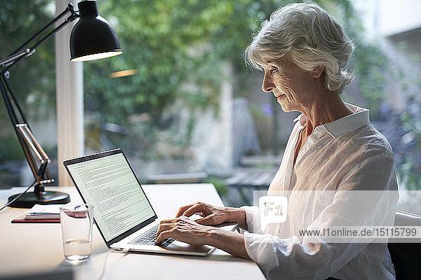 Lächelnde reife Geschäftsfrau sitzt am Schreibtisch mit Laptop