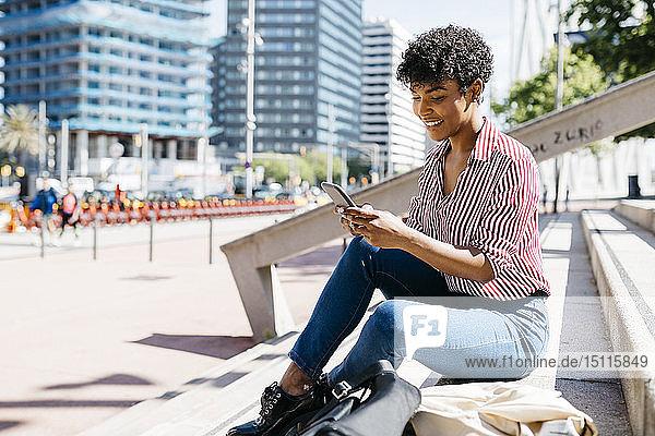 Geschäftsfrau mit Smartphone  die auf einer Treppe sitzt