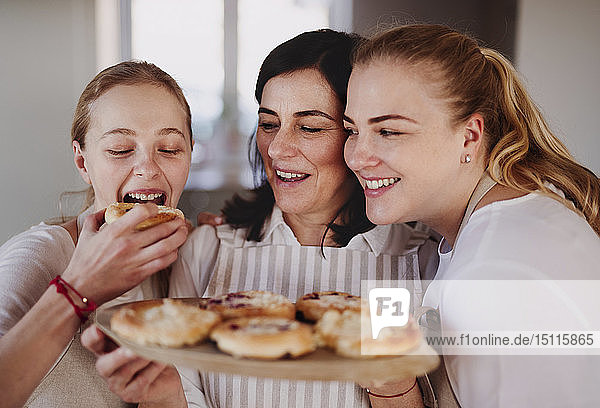 Daughters eating cake  served by their mother