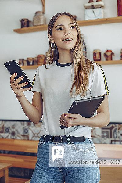 Porträt einer jungen Frau  die in einem Cafe eine Tablette hält