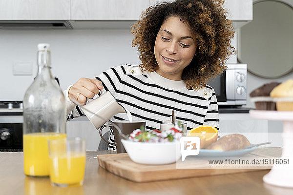 Woman sitting in kitchen  having breakfast