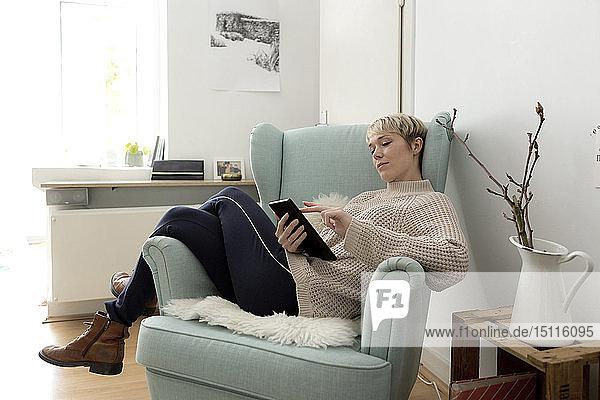 Entspannte Frau sitzt zu Hause im Sessel und benutzt Tablette