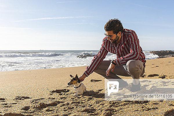 Portugal  Porto  junger Mann streichelt seinen Hund am Strand