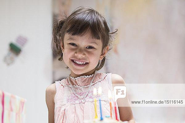 Porträt eines glücklichen kleinen Mädchens mit brennenden Kerzen auf Geburtstagskuchen
