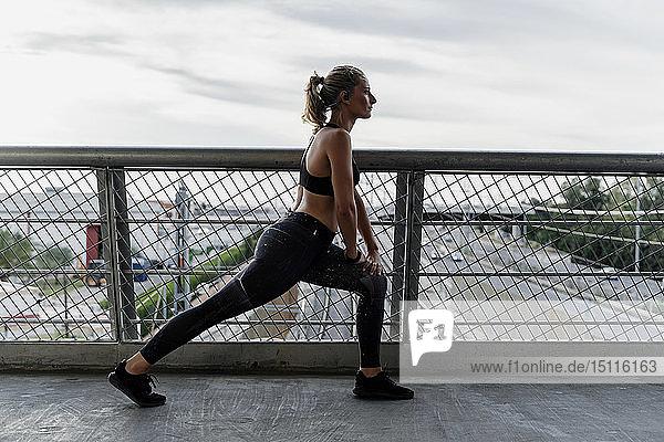 Sportliche Frau wärmt sich auf einer Brücke auf