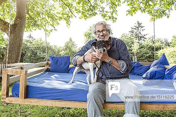 Älterer Mann entspannt sich auf einem Schaukelbett in seinem Garten