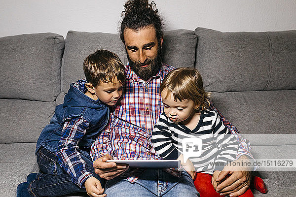 Father sitting on the couch with his children watching movies on digital tablet