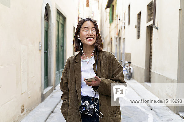 Italy  Florence  happy young woman with earphones and cell phone in an alley