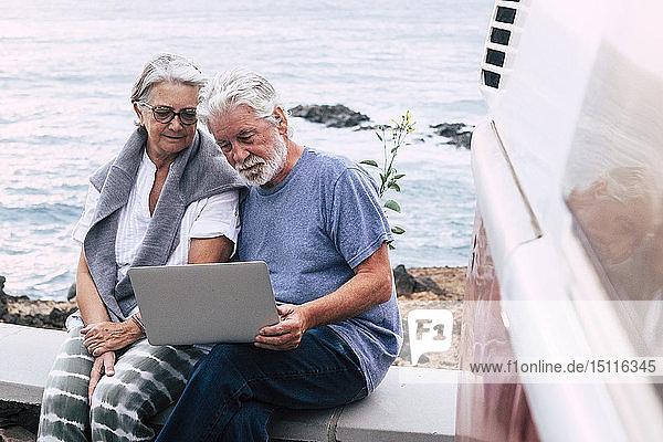 Älteres Ehepaar reist in einem Oldtimer-Lieferwagen  benutzt einen Laptop und sitzt auf einer Mauer am Meer