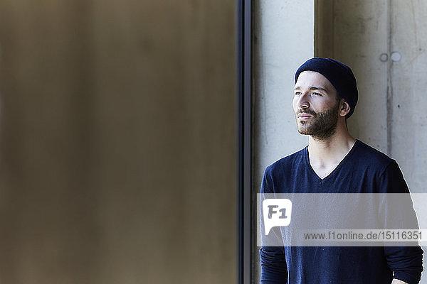 Junger Mann mit Mütze  der aus dem Fenster schaut