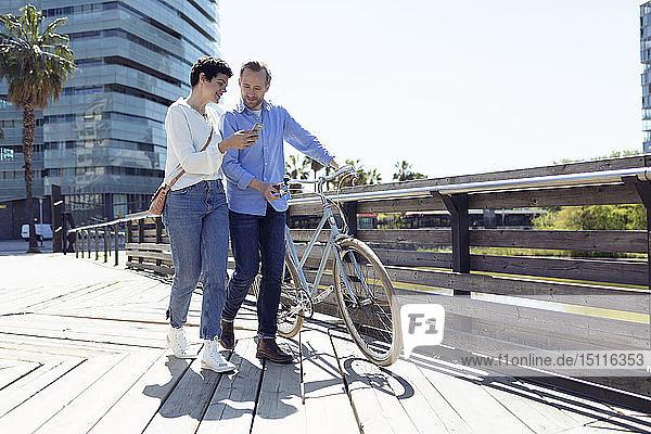 Paar mit Fahrrad  Frau mit Smartphone in Barcelona