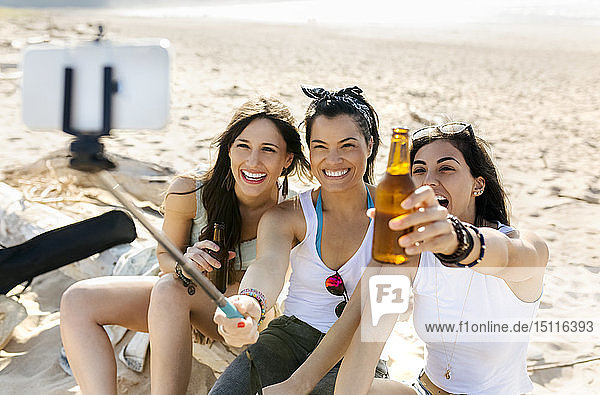 Happy female friends with beer bottles taking a selfie on the beach